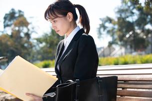 書類を見て真剣な顔をしているスーツ姿の女性の写真素材 [FYI02838300]