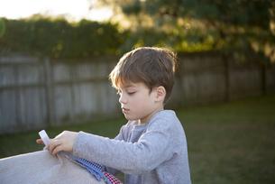庭でシーツでテントを作っている男の子の写真素材 [FYI02838309]