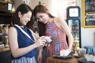 カフェでケーキの写真を撮っている二人の写真素材 [FYI02838335]