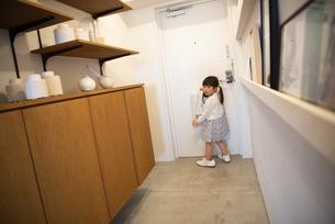 母親の靴を履いて玄関にいる女の子の写真素材 [FYI02838336]