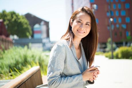 スマホを持ってベンチに座っている女性の写真素材 [FYI02838341]