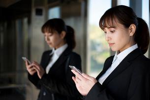 エレベーターの中でスマホを見ているスーツ姿の女性の写真素材 [FYI02838343]