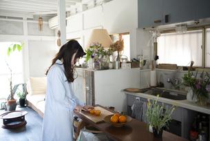 台所でオレンジを切っている女性の写真素材 [FYI02838347]