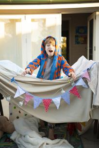 シーツで作ったテントから出ている男の子の写真素材 [FYI02838359]