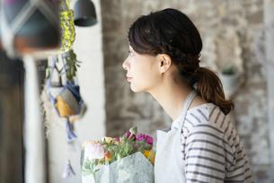 花束を持って外を眺めている店員の女性の写真素材 [FYI02838366]