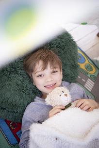 シーツで作ったテントの中で寝転んでいる男の子の写真素材 [FYI02838399]