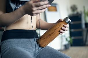 ウォーターボトルを持って音楽を聴いている女性の写真素材 [FYI02838400]