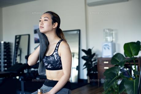 ジムで汗を拭きながら休憩をしている女性の写真素材 [FYI02838409]