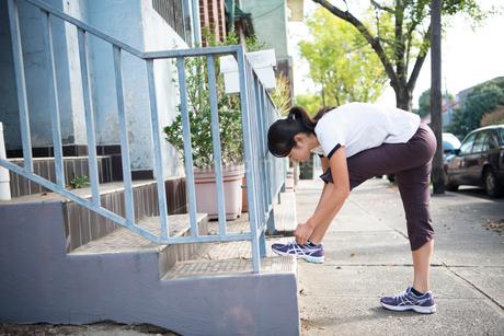 靴紐を結んでいるトレーニングウェアの女性の写真素材 [FYI02838420]