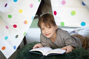 シーツで作ったテントの中で本を読んでいる男の子の写真素材 [FYI02838429]