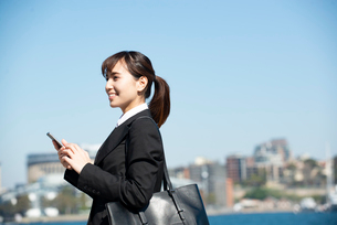 スマホを持って笑っているスーツ姿の女性の写真素材 [FYI02838432]