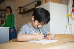 キッチンにいる母親と勉強中の男の子の写真素材 [FYI02838463]
