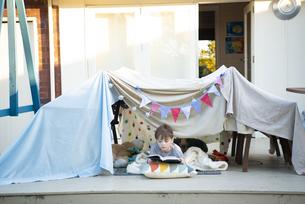 シーツで作ったテントの中で本を読んでいる男の子の写真素材 [FYI02838467]