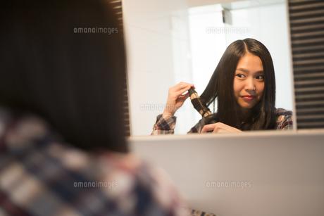 髪の毛を巻いている女性の写真素材 [FYI02838473]