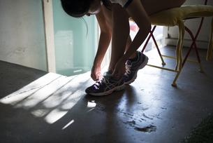 スニーカーの靴紐を結んでいる女性の写真素材 [FYI02838505]
