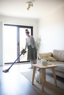 リビングで掃除機をかけている女性と猫の写真素材 [FYI02838509]