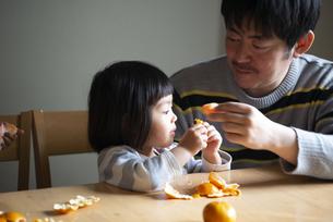 みかんを剥いている親子の写真素材 [FYI02838512]