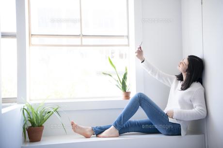 窓辺に座ってスマホで自撮りをしている女性の写真素材 [FYI02838514]