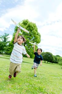 公園で模型飛行機を飛ばす子供たちの写真素材 [FYI02838534]