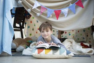 シーツで作ったテントの中で本を読んでいる男の子の写真素材 [FYI02838554]