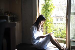窓辺に座って本を読んでいる女性の写真素材 [FYI02838584]