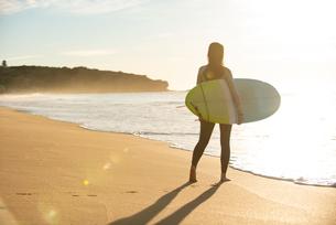 サーフボードを抱えて砂浜を歩いている女性の写真素材 [FYI02838594]