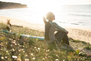 ビーチに座っているウェットスーツ姿の女性の写真素材 [FYI02838629]