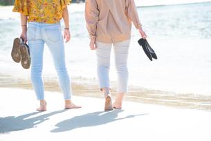 ビーチを裸足で歩いている女性2人の後ろ姿の写真素材 [FYI02838667]