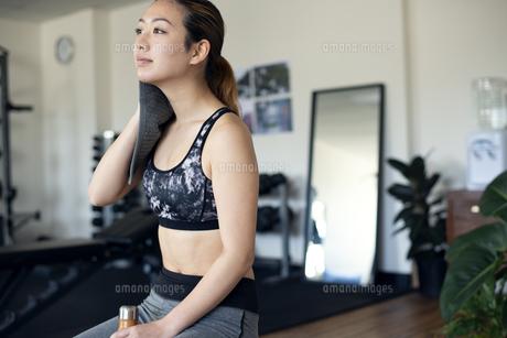 ジムで汗を拭きながら休憩をしている女性の写真素材 [FYI02838732]