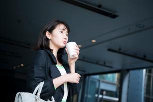 コーヒーを持って遠くを見ている女性の写真素材 [FYI02838733]