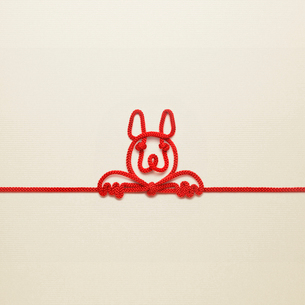 赤い紐でつくった犬(戌)のイメージの写真素材 [FYI02838810]