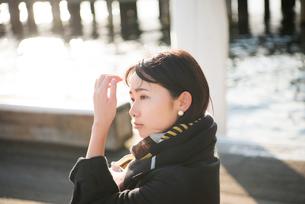 水辺に佇んでいる女性の写真素材 [FYI02838835]