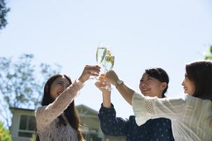ガーデンパーティで乾杯をしている笑顔の女性3人の写真素材 [FYI02838874]