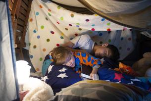 シーツで作ったテントの中で眠っている兄弟の写真素材 [FYI02838876]