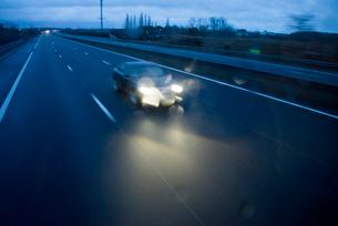 夕暮れの高速道路を走る車の写真素材 [FYI02838879]