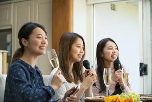 家でカラオケパーティをしている女性たちの写真素材 [FYI02838892]