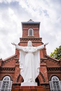 両腕を開くキリスト像越しの大曽教会の写真素材 [FYI02838961]
