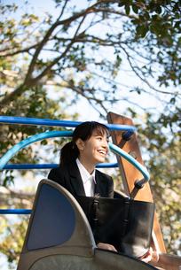 滑り台の上で笑っているスーツ姿の女性の写真素材 [FYI02838963]