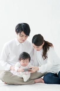 赤ちゃんと携帯電話を見る夫婦の写真素材 [FYI02839053]