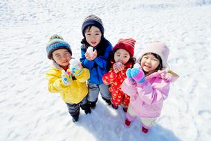 雪の公園で雪を持つ子供たちの写真素材 [FYI02839244]