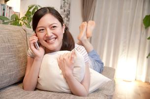 ソファで携帯電話で話す女性の写真素材 [FYI02839261]