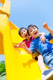 公園の滑り台で遊ぶ男の子2人の写真素材 [FYI02839369]
