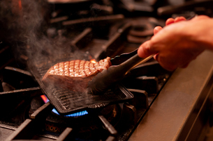 グリルで焼かれている赤味が残る肉の写真素材 [FYI02839484]