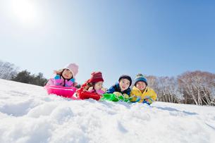 雪の公園でソリ遊びをする子供たちの写真素材 [FYI02839513]