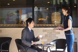 テラスでコーヒーを頼む男性の写真素材 [FYI02839630]