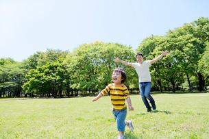公園を走る父と息子の写真素材 [FYI02839667]