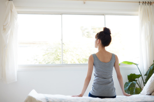 ベッドに腰掛ける女性の写真素材 [FYI02839710]