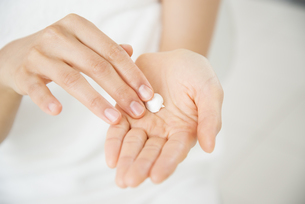 クリームを手に取っている女性の手元の写真素材 [FYI02839716]