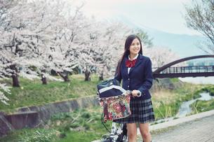 桜並木で自転車を押す女子高生の写真素材 [FYI02839800]