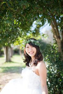 森の中で笑っているウェディングドレス姿の女性の写真素材 [FYI02839811]